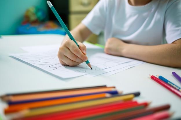 La bambina disegna mentre è seduta a un tavolo in una stanza sullo sfondo del muro