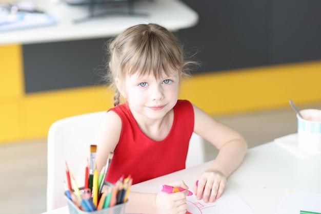 La bambina disegna con matite colorate su carta sviluppo del pensiero creativo nei bambini