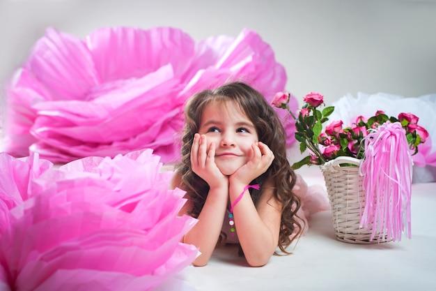 Bambina che sogna che osserva in su vicino al fiore enorme dalla carta