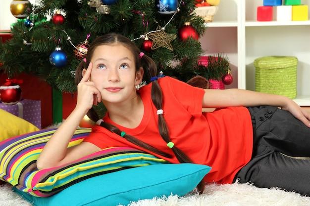 Bambina che sogna vicino all'albero di natale