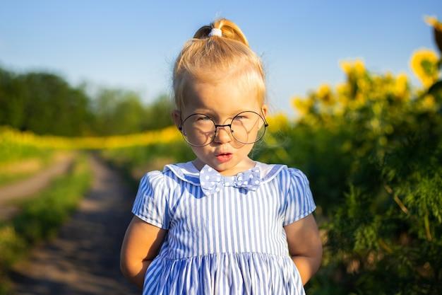 Bambina in un vestito e occhiali sullo sfondo di un campo di girasoli. faccia emotiva.