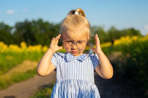 Bambina in un vestito e occhiali sullo sfondo di un campo di girasoli.