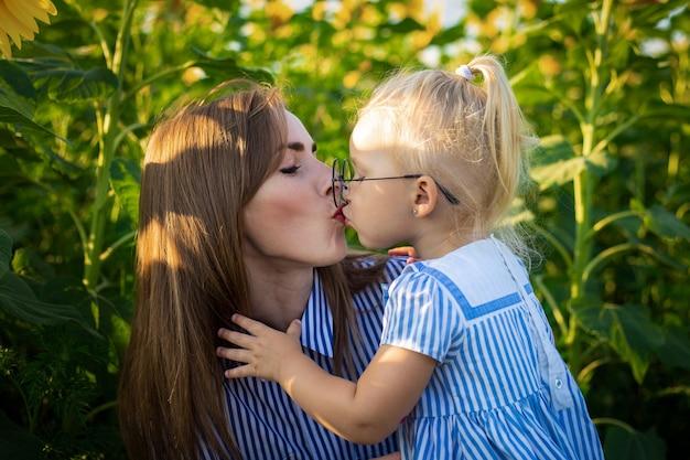Bambina in un vestito e occhiali bacia la madre su un campo di girasoli.