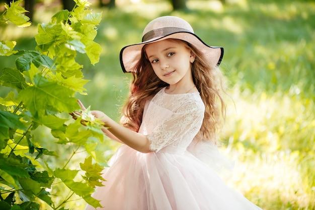 Bambina in un vestito e cappello nel parco