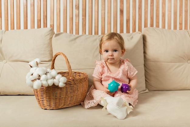 La bambina in un vestito si siede e guarda la telecamera su un divano beige con un cesto e uova colorate