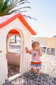 La bambina in un vestito sta su un campo da giuoco del ciottolo vicino ad una casa del giocattolo