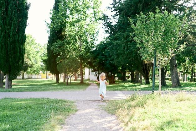 La bambina in un vestito cammina lungo un sentiero di ghiaia in un parco verde