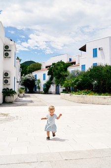 La bambina in un vestito cammina nel cortile sullo sfondo di case a due piani e vegetazione