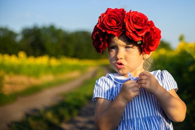 Bambina in un vestito e una corona di grandi fiori rossi sullo sfondo di un campo di girasoli. faccia emotiva.