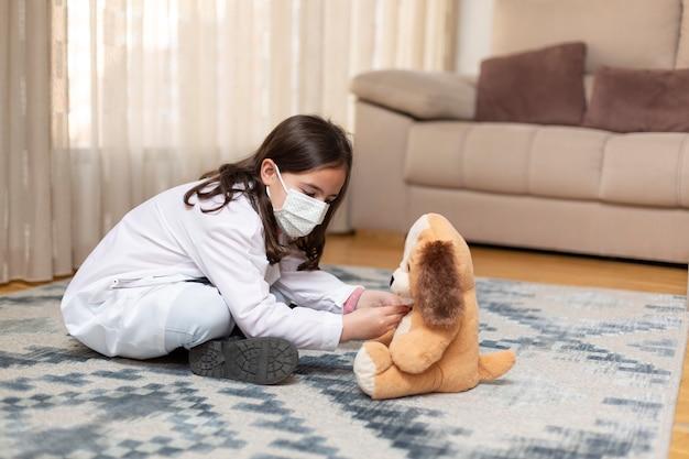 Bambina vestita come un medico che esamina un orsacchiotto di peluche a casa