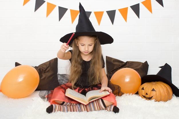 Bambina vestita da strega con in mano un libro di stregoneria mentre celebra halloween a casa