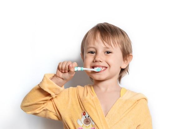 Bambina vestita in accappatoio lavarsi i denti