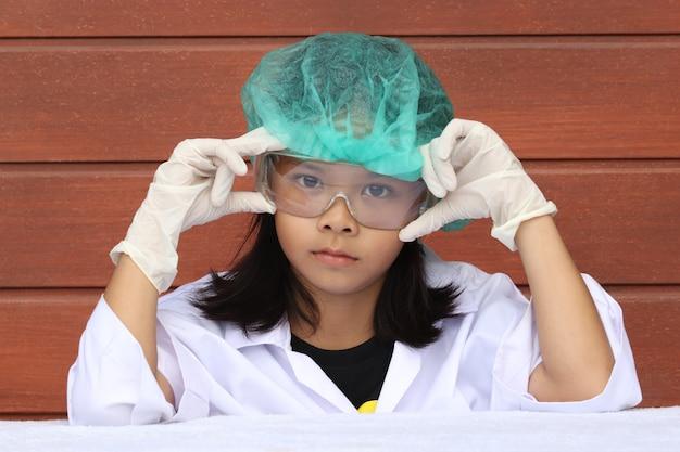Bambina vestita da medico con cappello, occhiali e guanti su fondo di legno