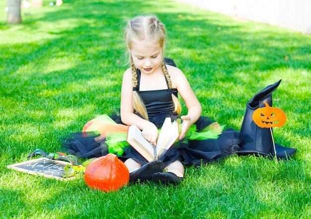 Una bambina vestita con un costume da strega, un cappello nero e un rossetto nero sulle labbra è seduta con un libro e tiene in mano una bacchetta magica. halloween.