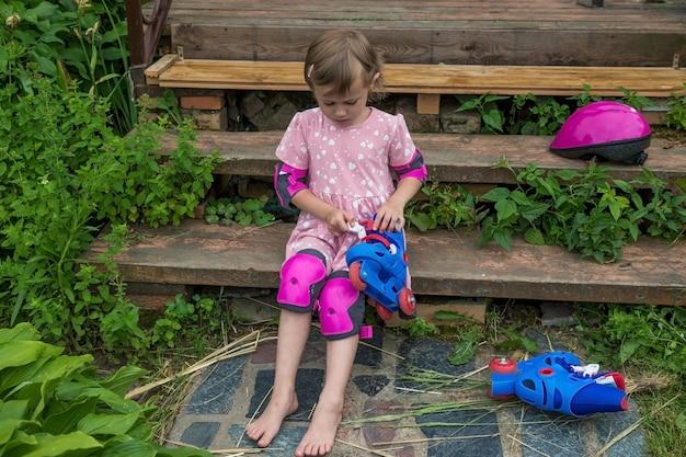 Una bambina veste i pattini a rotelle seduta sui gradini della sua casa di campagna.