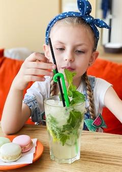 Bambina che beve mojito analcolico in un caffè