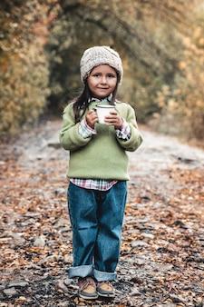 La bambina beve il tè nella sosta di autunno