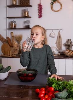 Una bambina beve acqua da un bicchiere su un tavolo di legno in cucina