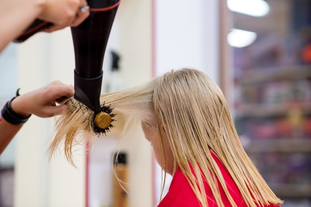Capelli asciutti della bambina nel negozio di barbiere.