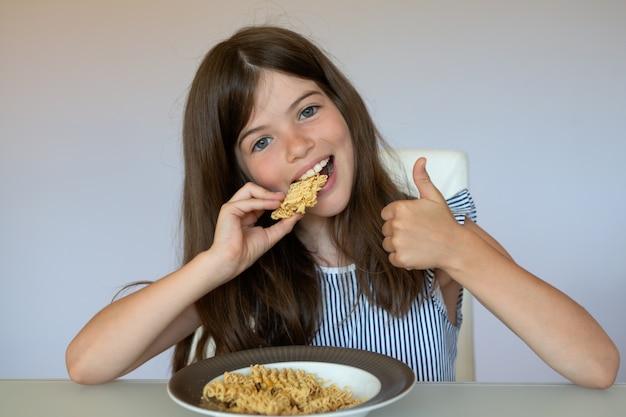 Bambina che mangia spaghetti istantanei cinesi