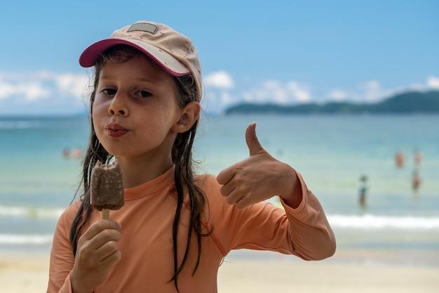 Bambina che mangia il gelato con spiaggia in background.