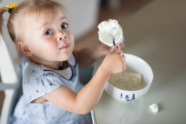 Bambina che mangia un cucchiaio di gelato da un piatto