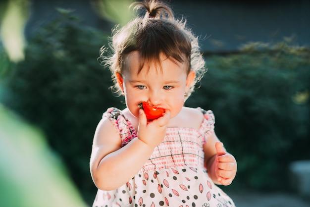 Una bambina che mangia un pomodoro. molto carino il controluce in giardino da solo
