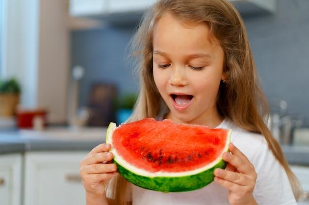 Bambina che mangia pezzo di anguria in cucina