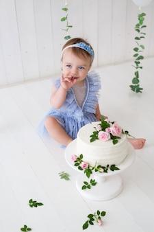 La bambina mangia la torta per il suo compleanno.