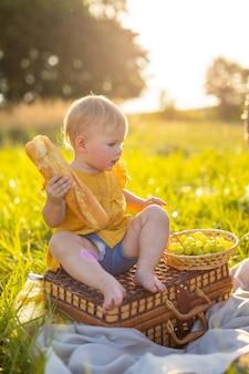 La bambina mangia baguette e frutta fresche durante un picnic alle luci del tramonto in natura