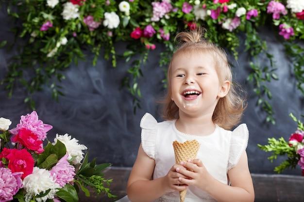 La bambina mangia il gelato e ride. una decorazione floreale in un interno. ritratto della bella ragazza emotiva