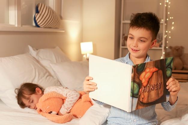 Bambina che si addormenta mentre suo fratello legge la storia della buonanotte a casa