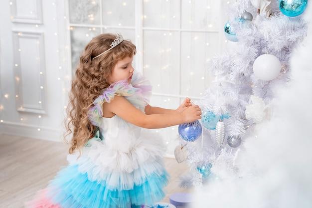 Bambina in costume che decora un enorme albero di natale bianco