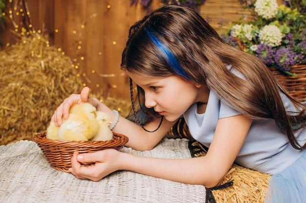 Bambina in una fattoria con polli pasqua ecologia e concetto di agricoltura