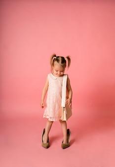 La bambina in un vestito festivo e le scarpe di sua madre e con una borsa guarda in basso su una superficie rosa con un posto per il testo