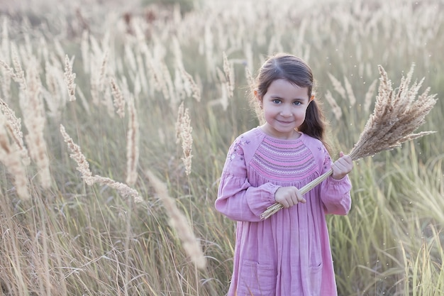 La bambina nel campo tiene un mazzo di grano.