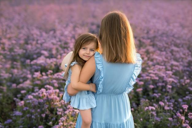 La bambina in un campo di fiori viola abbraccia teneramente sua madre.