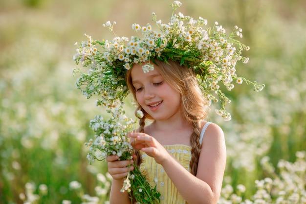 Bambina in un campo con una corona che tiene un mazzo di sorrisi di fiori selvatici