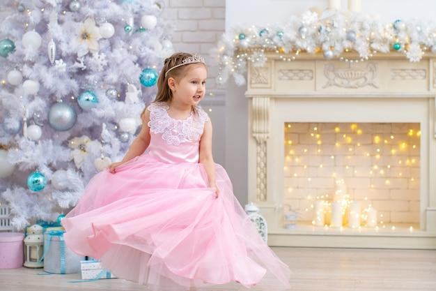 Una bambina con un soffice vestito rosa gira in soggiorno vicino al camino e all'albero di natale, ballando sviluppando il vestito. un bambino nella hall con un grande albero di natale bianco
