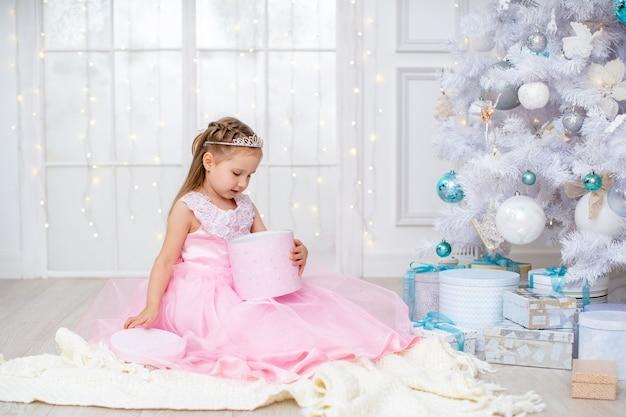 Una bambina in un soffice abito rosa apre una scatola con doni nel soggiorno vicino all'albero di natale, gioisce del regalo ricevuto. un bambino nella hall con un grande albero di natale bianco