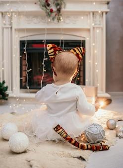 Una bambina in un soffice abito bianco e una fascia con le orecchie di tigre è seduta con la schiena in una stanza vicino al camino