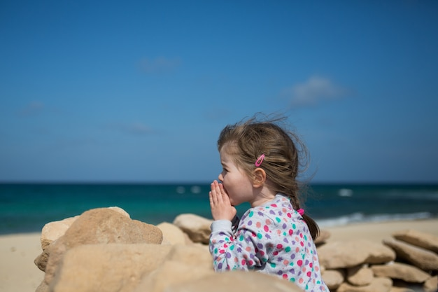 La bambina ha piegato le mani in preghiera, pregando