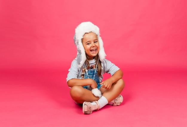 La bambina in un cappello invernale di pelliccia si siede su uno sfondo rosa. concetto di vestiti caldi di moda invernale. cappello di lana caldo per bambini