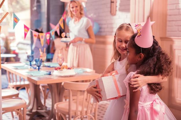 Bambina che riceve i regali di compleanno dai suoi amici