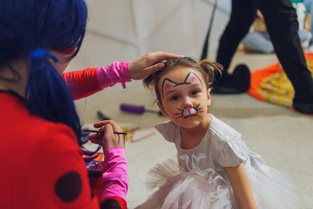 Bambina che si fa dipingere il viso a forma di farfalla dall'artista della pittura del viso. trucco. persone reali. copia spazio.