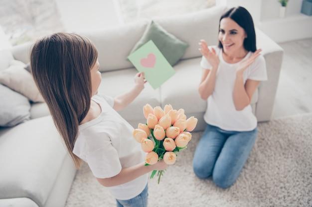 La bambina dà i fiori dei tulipani della cartolina del regalo di compleanno della mamma in casa all'interno