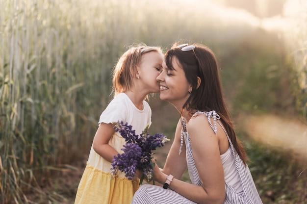 Una bambina regala un mazzo di lupini a sua madre sul campo d'estate. concetto di amore e famiglia felice