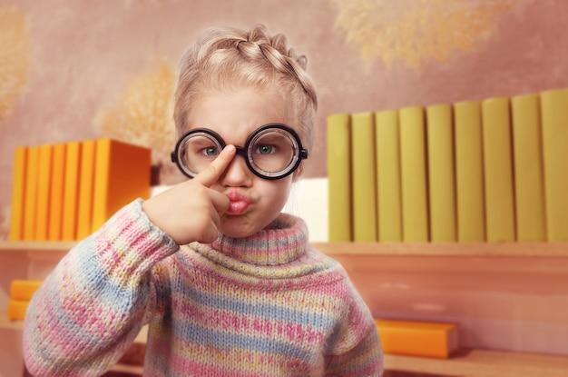 La bambina con gli occhiali fa le facce