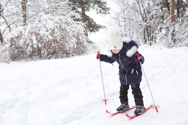 La bambina scivola giù per il pendio con gli sci di plastica rossi con i bastoni