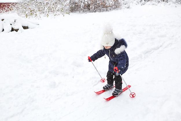 Una bambina scivola giù per il pendio con gli sci di plastica rossi.